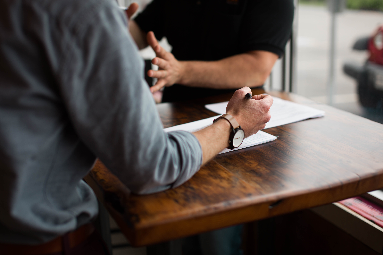 To mænd holder møde over et bord