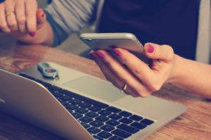 Kvinde sidder ved hendes computer med hendes telefon i hånden