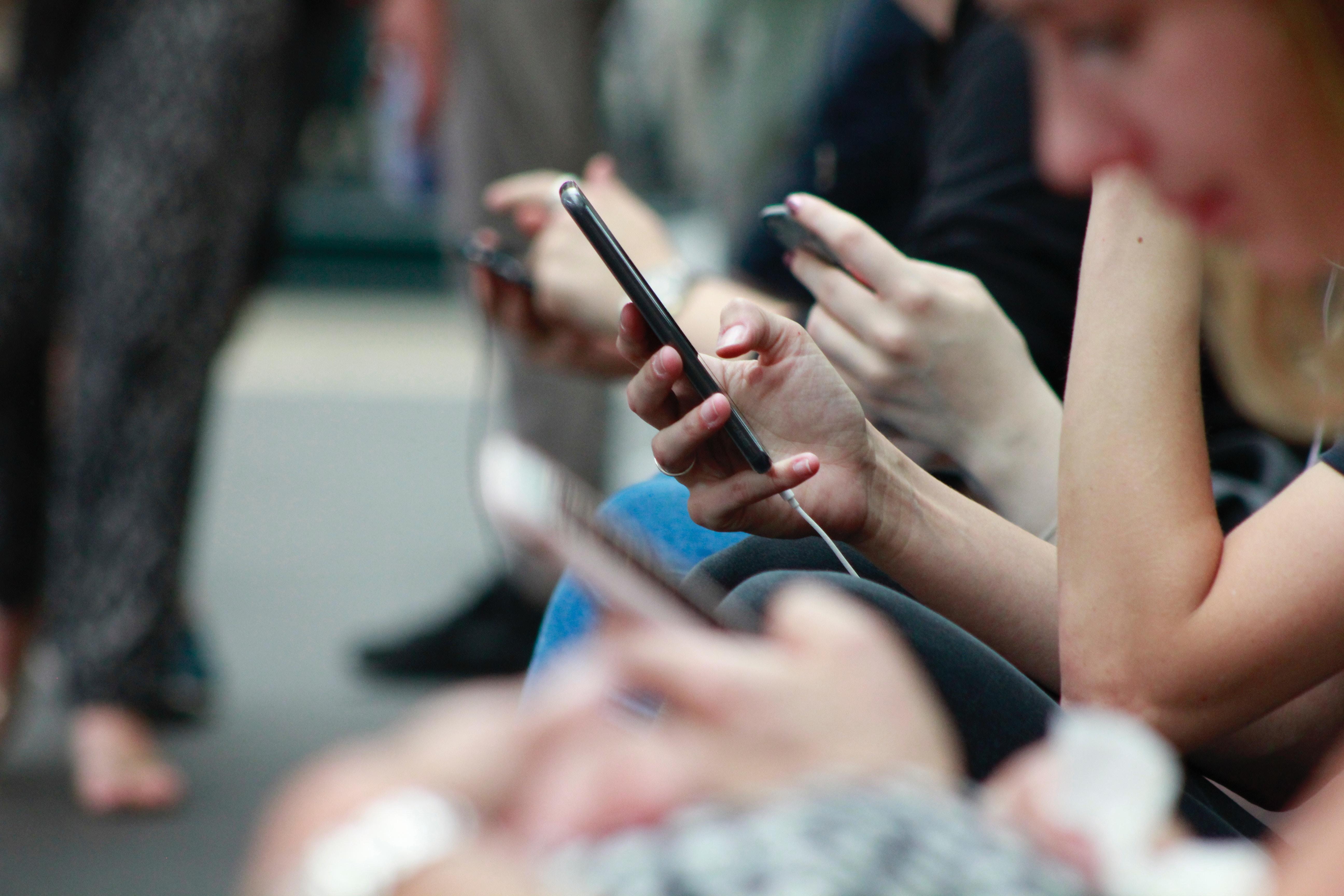 Flere personer sidder og kigger i deres telefoner